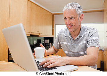Man using a laptop while drinking tea in a kitchen