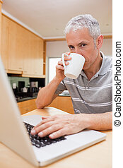 Portrait of a man using a laptop while drinking tea in a...