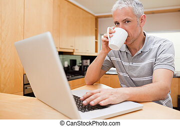 Man using a notebook while drinking coffee in a kitchen