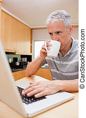 Portrait of a man using a laptop while drinking coffee in a...