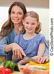 Portrait of a woman slicing bell pepper with her daughter