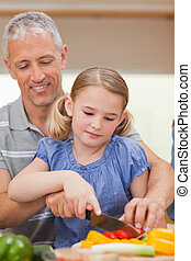 Portrait of a father showing his daughter how to cook