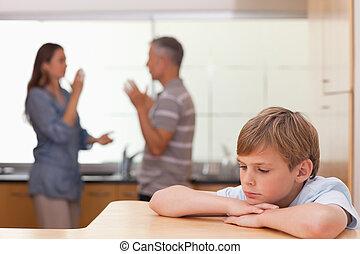 Sad little boy hearing his parents having am argument