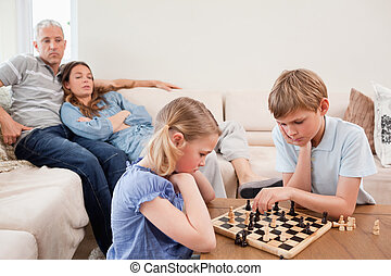 Siblings playing chess in front of their parents