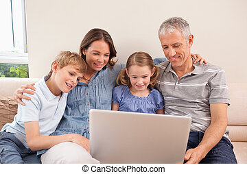 Family sitting on a sofa using a notebook