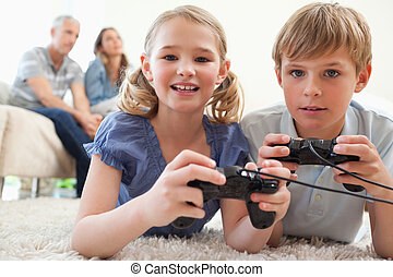 Playful siblings playing video games with their parents on the background in a living room