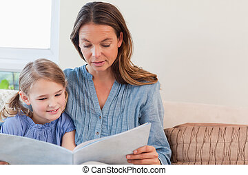 Mother reading a book to her daughter in a living room
