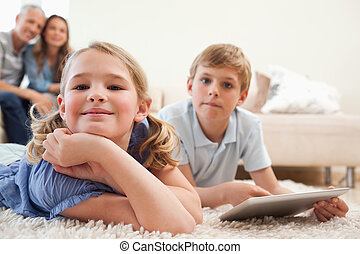 Happy siblings using a tablet computer with their parents on the background in a living room