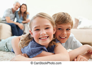 Happy siblings posing on a carpet with their parents on the...