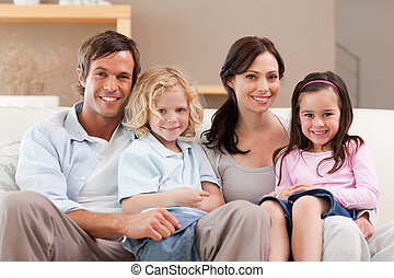 Cute family watching television together in a living room