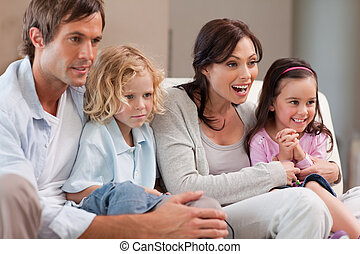 Cheerful family watching television together in a living...