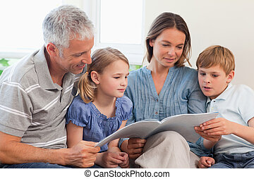 Family reading a book together in a living room