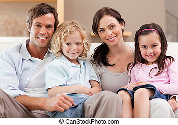 Happy family watching television together in a living room