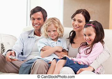 Smiling family watching television together in a living room