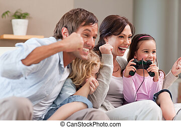 Positive family playing video games together in a living...