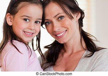 Close up of a girl and her mother smiling at the camera