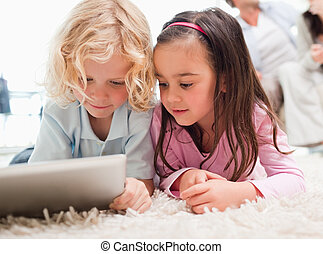 Children using a tablet computer while their parents are in...