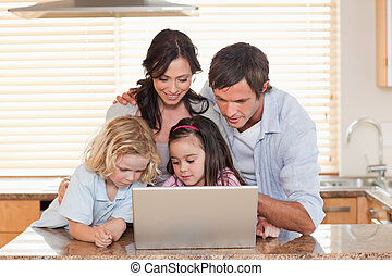 Family using a notebook together in a kitchen