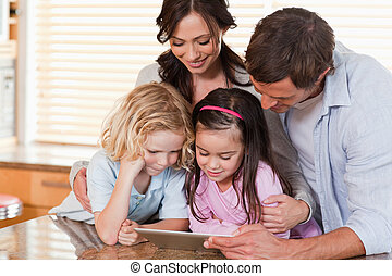 Happy family using a tablet computer together in a kitchen