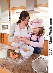 Portrait of a mother and her happy daughter baking in a...