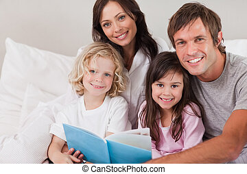 Happy family reading a book in a bedroom