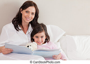 Happy mother reading a story to her daughter