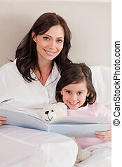 Portrait of a happy mother reading a story to her daughter