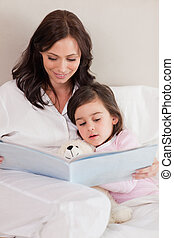 Portrait of a mother reading a story to her daughter