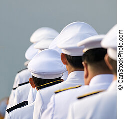 Military officers in parade uniforms seen from behind....