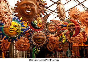 A lot of beautiful handmade masks of sun in the handmade...