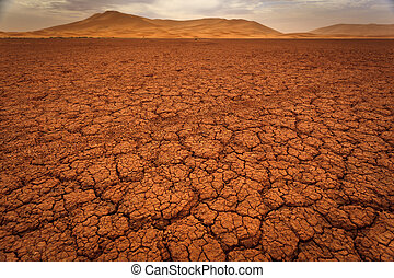 Cracked pattern of dry lake bed and sand dunes in Sahara Desert Morocco