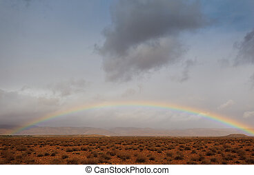 Full rainbow over the Sahara Desert in Africa with partly cloudy sky
