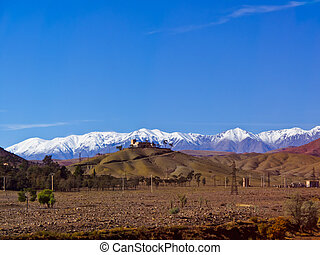 Mosque on hilltop with snow capped Altas Mountains in the background