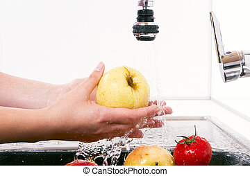 The ripe apples are washed in the kitchen - Women wash the...