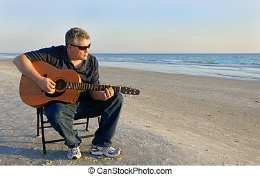 Blues at the Sea - A middle aged man playing a guitar at the...