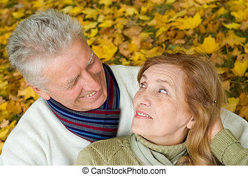 olds at park - portrait of a pretty elderly couple at autumn...