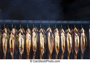 Smoking brook trout fish in an traditional oven