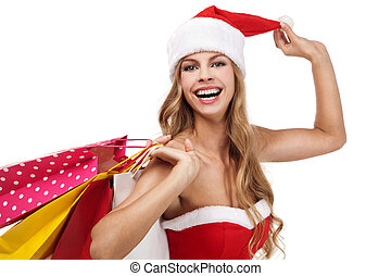 Portrait of a Christmas woman in santa costume holding a shopping bags over white background