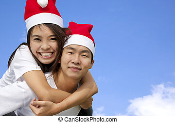 Young happy asian couple in Christmas hats