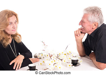 olds at table - pretty old couple sitting at table on white