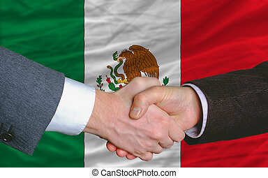 businessmen handshake after good deal in front of mexico...