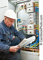 Electrician at wiring with working drawings - One...