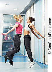healthy woman jumping at fitness training gym - two...