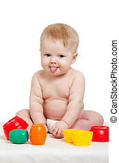 Cute little baby is playing with color toys, isolated over white