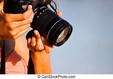 Girl Taking a Picture - A girls hands holding a DSLR camera...