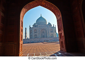 Taj Mahal in India in backlight seen from the arch of the...