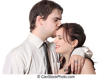 Cute young couple with man kissing womans forehead, together...