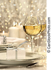 Festive table setting with silver ribbon gift on plate