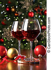 Glasses of red wine in front of Christmas tree for the...