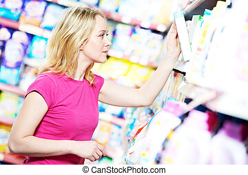 woman at household chemistry shopping